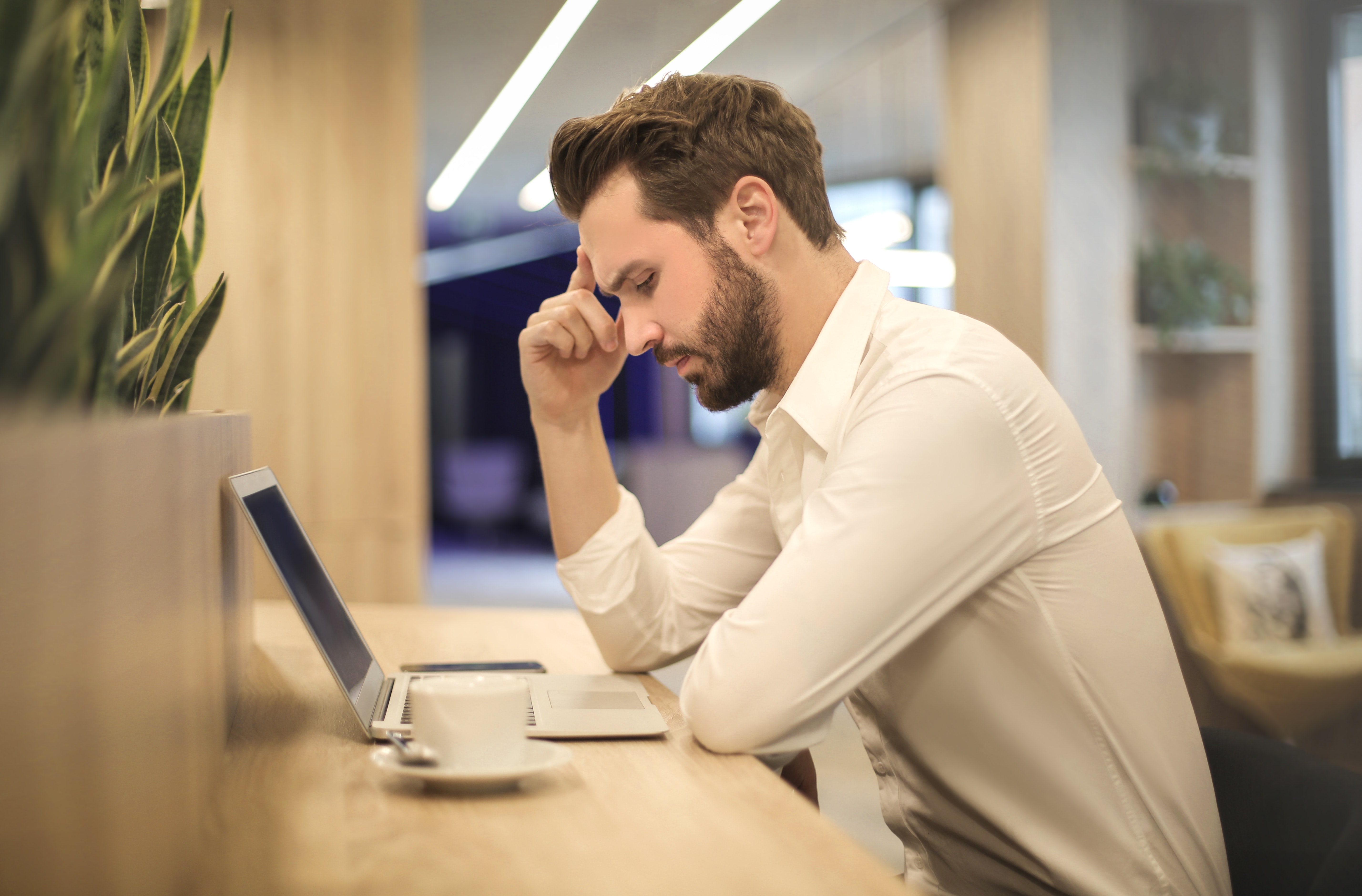 Man at computer holding his head and looking worried.