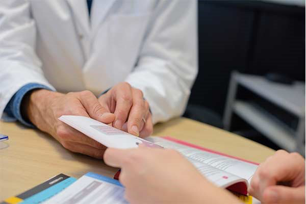 Photo of a doctor handing a brochure to a patient