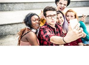 A group of teens taking a selfie with a cell phone