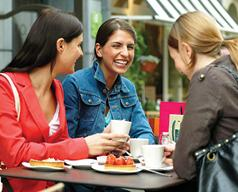 Photo of three young women eating and laughing