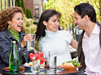 Image of three hispanic people enjoying dinner